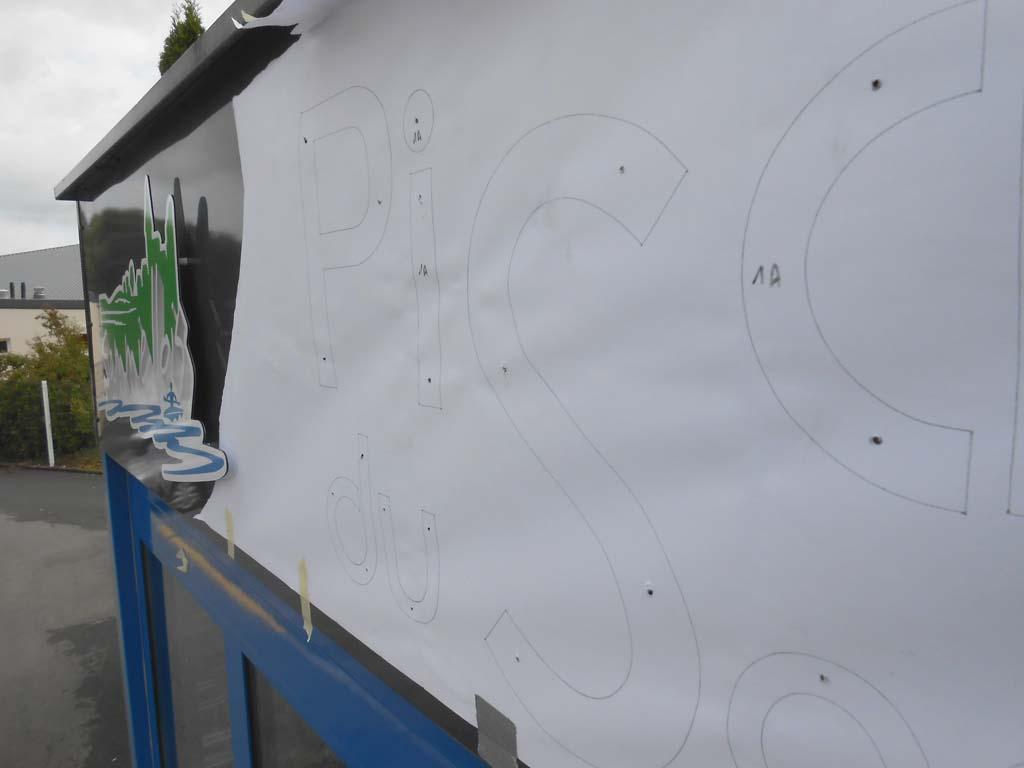 Mise en place du plan de pose pour le perçage des trous de fixation des entretoises qui maintiendront les lettres découpées en dibond sur Saint-Mihiel 55