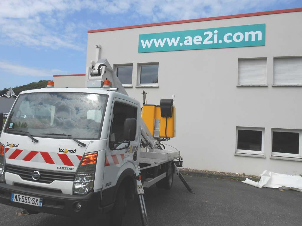 Bandeau enseigne de grandes dimension posée en hauteur sur façade avec une nacelle élévatrice à Nancy près de Metz