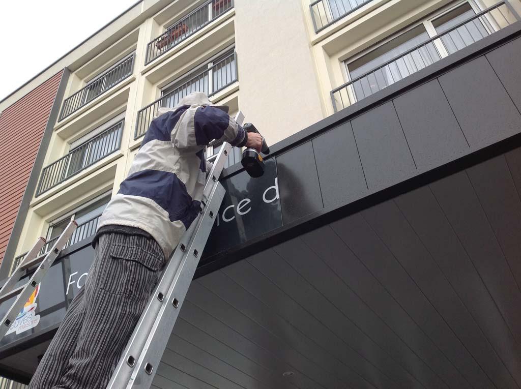 Pose d'un panneau publicitaire sur une façade à Neuves-Maisons 54 près de Jarville en Lorraine