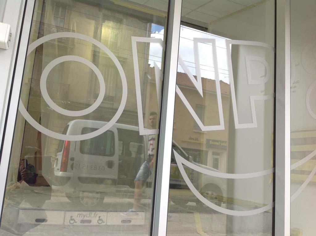 Pose de décors en film adhésif effet dépoli sur les vitres d'une porte automatique pour l'ONPA à Nancy