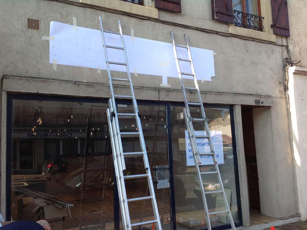 Positionnement du plan de pose pour la fixation des lettres en dibond sur la façade du magasin Salines Optic à Dombasles 54