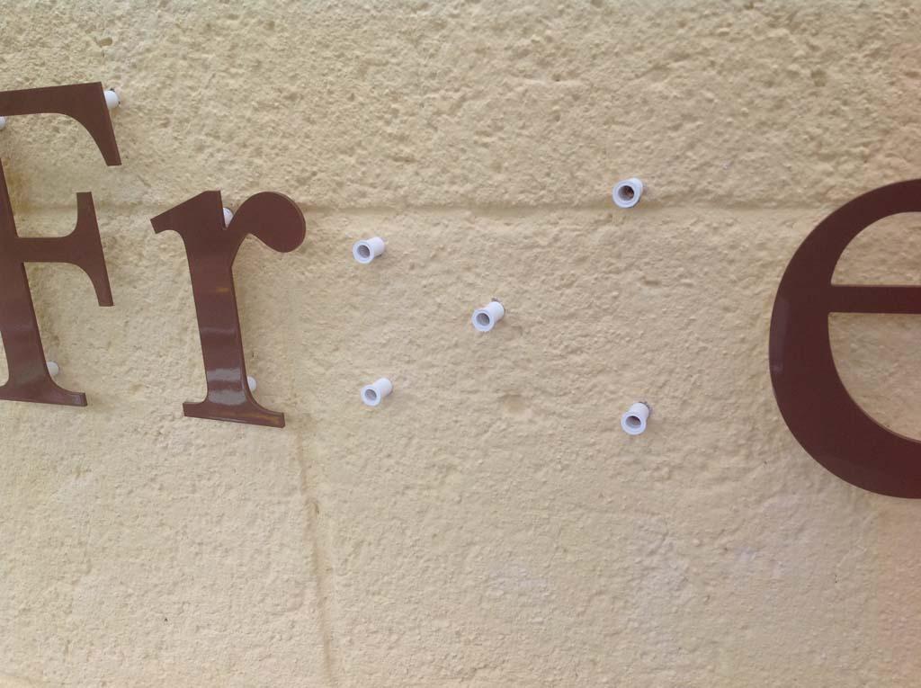 Lettres en relief posées en retrait avec entretoises
