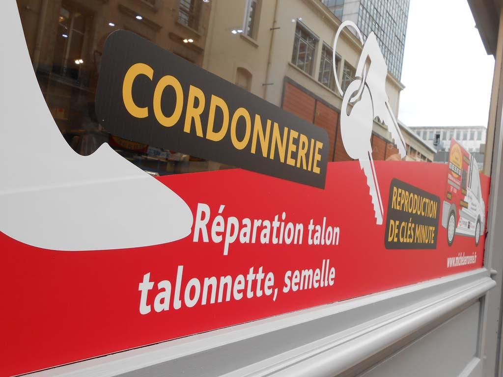Habillage publicitaire sur vitrine commerciale en vinyle adhésif polymère avec impression numérique quadri + plastification de protection rendu mat anti UV à Nancy ville !