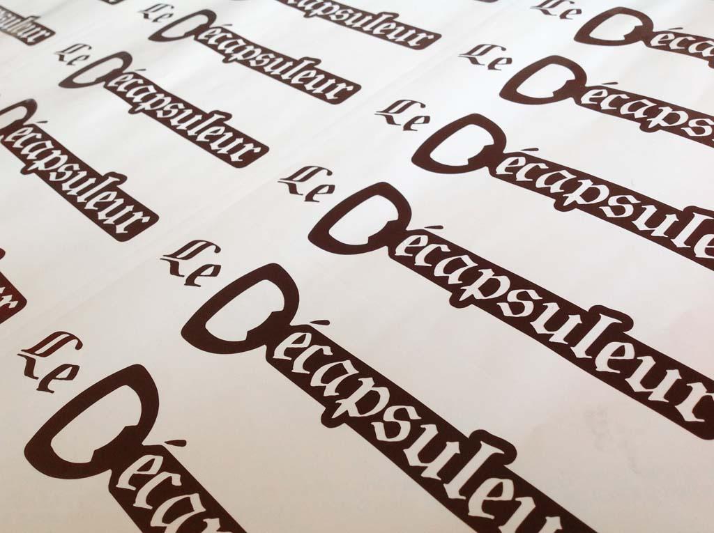 Planches de logos en adhésif découpé teinté masse pour coller sur les coffrets en bois de la cave à bière Le Décapsuleur basée à Pont Saint Vincent près de Nancy !